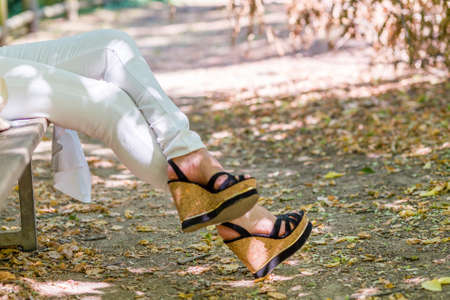 legs of woman sitting on bench in white trousers and high platform shoes