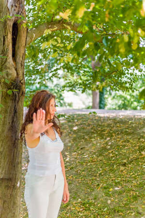 buxom: Stop and talk to my hand gesture by buxom over 40 woman with negative feelings against green garden background with copy space