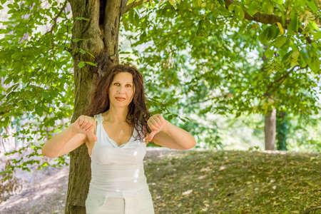 tetona: tetona con clase Mujer madura que da los pulgares abajo gesto mirando a la c�mara contra el fondo verde jard�n con espacio de copia