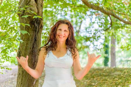 tetona: Cierre de tetona mujer madura con clase sonriendo a la cámara mientras hace la muestra de Shaka bienvenida contra el fondo verde jardín, con espacio de copia