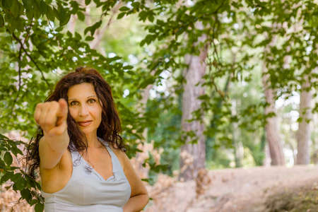 looking at viewer: buxom middle-aged woman dressed in white and with long brown wavy hair with pointing the finger of her right hand toward the viewer looking into camera Stock Photo
