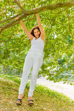 buxom: happy buxom woman dressed in white swinging from tree branch in a garden Stock Photo