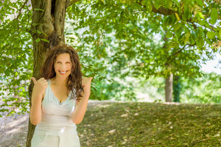 buxom: Cheerful buxom classy mature woman smiling at the camera and showing thumbs up against green garden background with copy space Stock Photo