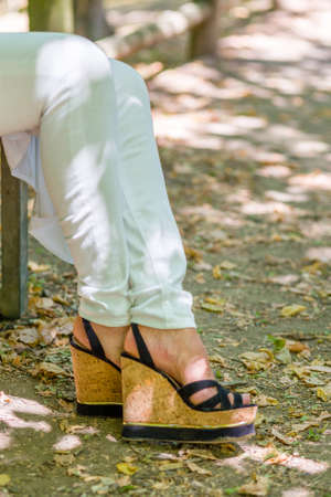 distension: legs of woman sitting on bench in white trousers and high platform shoes