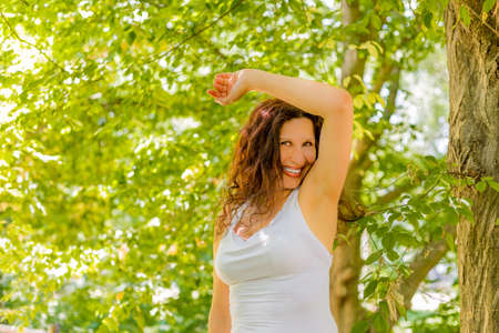 armpits: menopausal woman is happy and smiles sniffing her armpits  because her sweat does not stink