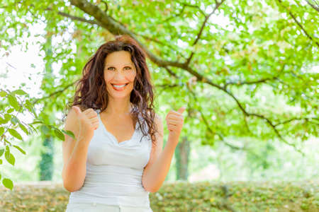 buxom: Cute buxom middle-aged woman smiling at the camera and showing thumbs up against green garden background with copy space