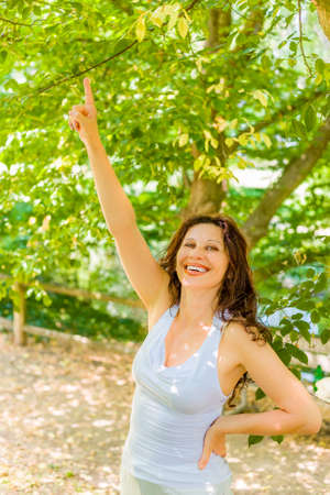 Happy menopausal woman with long brown wavy hair smiles while pointing the finger of right hand upward