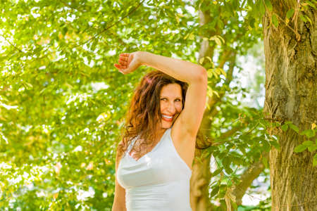menopausal woman is happy and smiles sniffing her armpits  because her sweat does not stink
