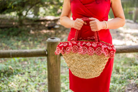 30 to 40 year old: female hands holding a bag in a country style made of raffia and red cloth with white flowers, the woman dressed in a red sheath dress is waiting nervously in a park Stock Photo