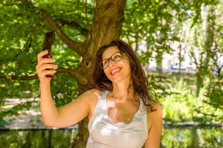 mature woman is taking a selfie with a phone for the elderly
