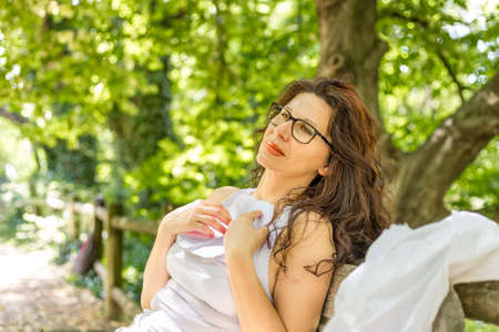 lost in thought: Romantic middle-aged woman with glasses  is holding white sheet of paper she has just read Stock Photo