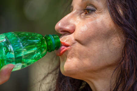 50 to 60 years: close up of menopausal mature woman drinking water from a plastic bottle
