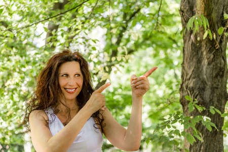 forties: menopausal woman points with her index fingers on her left, having a garden in the background