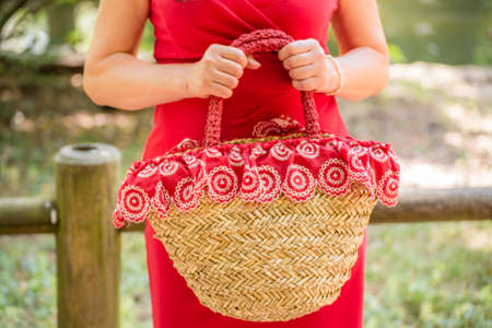 40 year old woman: female hands holding a bag in a country style made of raffia and red cloth with white flowers, the woman dressed in a red sheath dress is waiting nervously in a park Stock Photo
