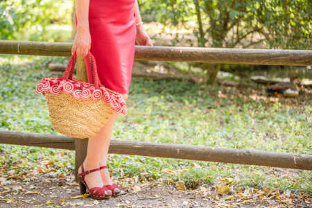 30 to 40 year old: long and shapely female legs of a woman who is waiting in a park, she is wearing a red tube dress, high-heeled sandals and holding a flower-filled bag in country style Stock Photo