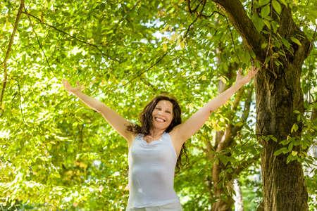 old age: felice donna in menopausa alza le braccia al cielo in un giardino, vivere con gioia il cambiamento di vita Archivio Fotografico