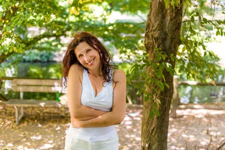 tenderly: charming and sweet menopausal woman hugging herself while tenderly smiling Stock Photo