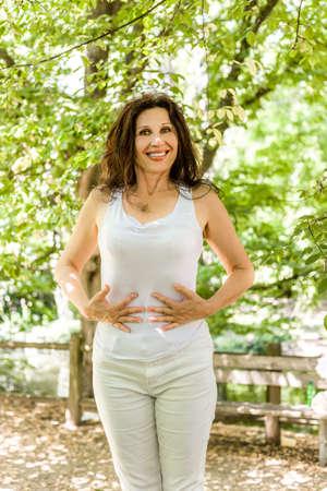 flat stomach: mujer menopáusica con la piel lisa es feliz porque ella perdió el peso y ahora tiene un vientre plano Foto de archivo