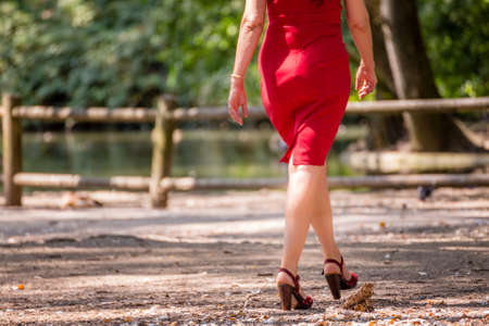 50 60 years: long and turned legs of woman bandaged in red pencil dress walking in the park on high heeled sandals