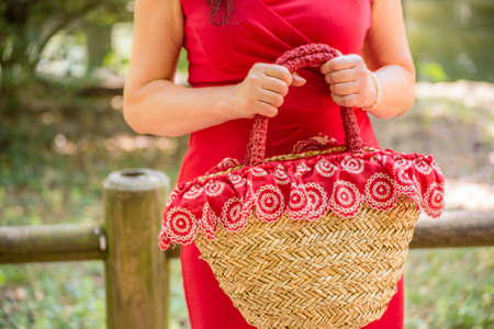 50 to 60 years: female hands holding a bag in a country style made of raffia and red cloth with white flowers, the woman dressed in a red sheath dress is waiting nervously in a park Stock Photo