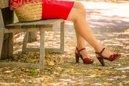 red tube: long and shapely female legs of a woman who is waiting on a bench in a park, she is wearing a red tube dress, high-heeled sandals and holding a flower-filled bag in country style Foto de archivo