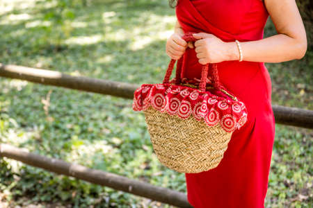 sheath: female hands holding a bag in a country style made of raffia and red cloth with white flowers, the woman dressed in a red sheath dress is waiting nervously in a park Stock Photo