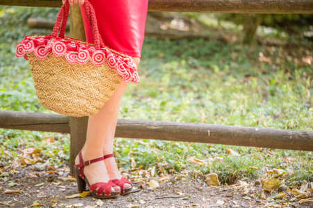 red tube: long and shapely female legs of a woman who is waiting in a park, she is wearing a red tube dress, high-heeled sandals and holding a flower-filled bag in country style Foto de archivo