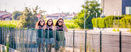 clones: multiplicity of attractive mature woman wearing a black lace top and vintage sunglasses while walking