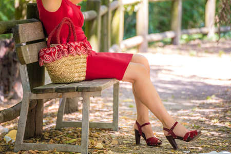 shapely legs: long and shapely female legs of a woman who is waiting on a bench in a park, she is wearing a red tube dress, high-heeled sandals and holding a flower-filled bag in country style Stock Photo