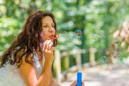 woman blowing: beautiful mature adult woman blowing soap bubbles Stock Photo