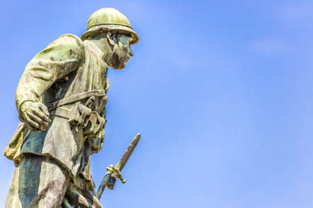 statue of a soldier of First World War leaning forward holding a bayonet rifle Stock Photo