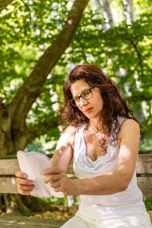안경과 긴 머리를 가진 매력적인 원시 여자 뻗은 팔을 들고 공원 벤치에 종이 착용 시트를 읽고