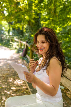 shortsighted: myopic woman chews the earpiece of her glasses while smiling and reading a worn sheet of paper on a park bench