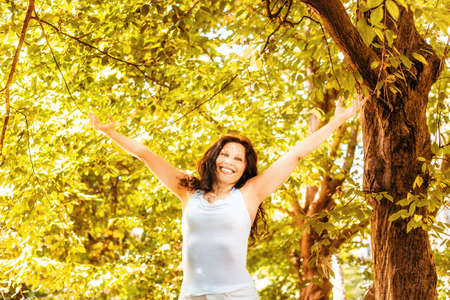 happy woman in menopause raises her arms to the sky in a garden, joyfully living the change of life Stockfoto
