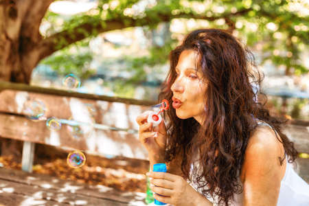 fascinating: Fascinating mature adult woman is having fun like a little girl blowing soap bubbles in a public park