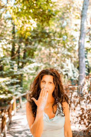 busty: Primer plano de mujer madura con clase tetona tapándose la boca con la mano contra el fondo verde jardín con espacio de copia