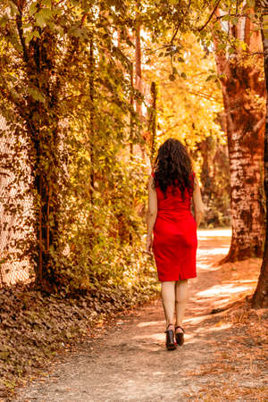 50 to 60 years: rear view of woman in red, high heels and cocktail dress who ventures into a path among trees