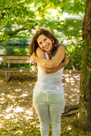 herself: Sunny menopausal woman smiles woman embracing herself