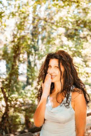 tetona: Cierre de tetona mujer madura con clase sonriendo a la cámara mientras se cubre la boca con la mano contra el fondo verde del jardín con espacio de copia