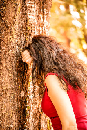 leaning against: woman in red with long wavy hair hiding face with arm leaning against a tree as if she were crying or if she were playing hide and seek