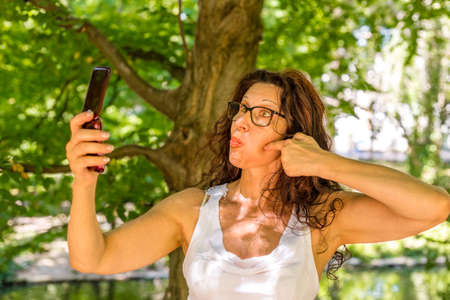 mature woman takes a selfie with a phone for the elderly grimacing