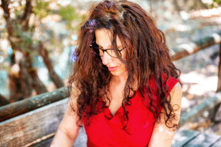 nerdy: gorgeous middle-aged woman in a red dress and long brown wavy hair is looking down wearing a pair of nerdy eyeglasses