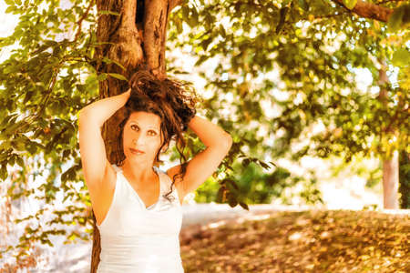 putting up: Sexy mature woman in white dress putting up her brown hair leaning against a tree in a garden background Stock Photo
