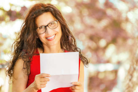 30 to 40 year old: gorgeous middle-aged woman in a red dress and long brown wavy hair is reading a paper and smiling while wearing a pair of nerdy eyeglasses in a garden Stock Photo