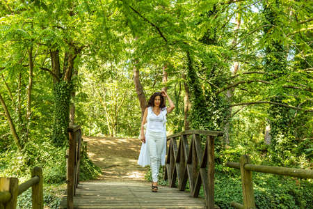 high  heeled: woman with high heeled sandals walking on a wooden bridge in a park