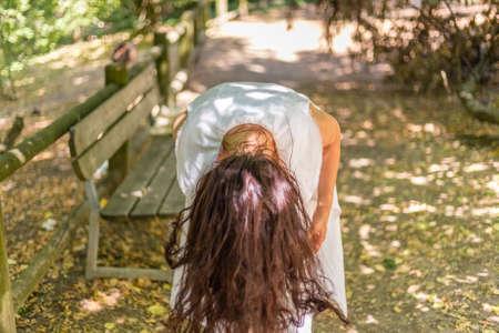 dangling: woman bends showing dangling hair Stock Photo