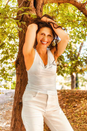 mature sexy woman: Sexy mature woman in white dress putting up her brown hair leaning against a tree in a garden background Stock Photo