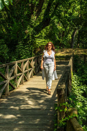 woman sandals: woman with high heeled sandals walking on a wooden bridge in a park