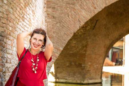 tight dress: environmental portrait of sexy woman in red tight dress standing against the walls of an old bridge in the hamlet of an old Italian village, Comacchio, known as Little Venice