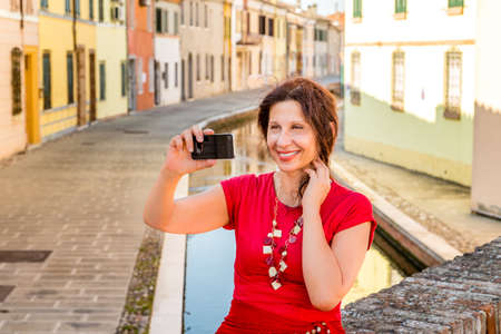 dress blowing in the wind: environmental portrait of Mediterranean woman in red dress taking a selfie while sitting on ancient bridge over water canals of an old village in Italy, Comacchio, known as Little Venice, wind is blowing hair